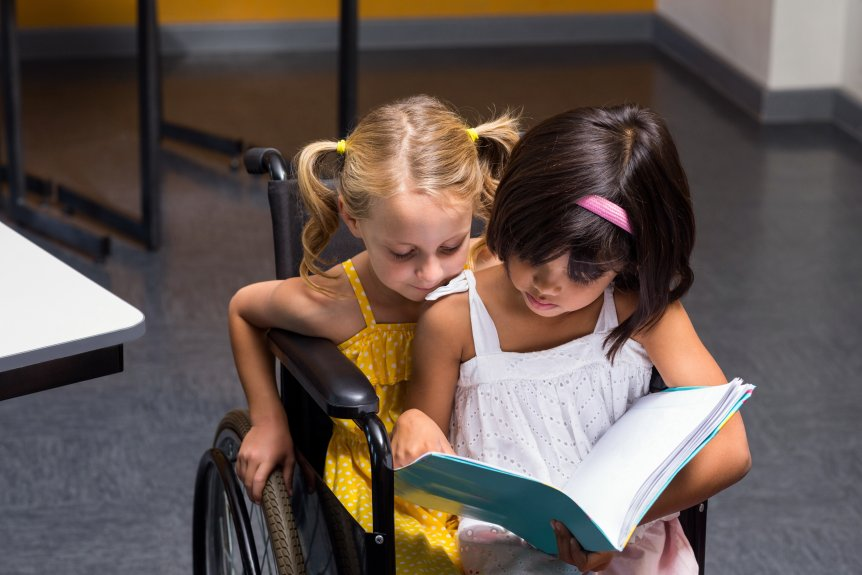 Two Children Reading in a Wheelchair